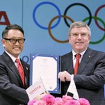 International Olympic Committee President Thomas Bach, right, and Toyota Motor Co. President Akio Toyoda hold their agreement document Friday.