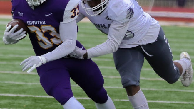 Kansas Wesleyan freshman Christopher Fluker (33) runs with the ball while being chased by an Avila defender during last Saturday's game at Graves Family Sports Complex.