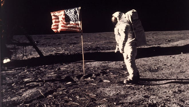"""Astronaut Edwin E. """"Buzz"""" Aldrin Jr. stands beside the U.S. flag unfurled on the moon during the Apollo 11 mission."""