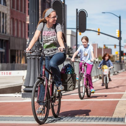 Stephanie Fisher bikes along the sidewalks downtown