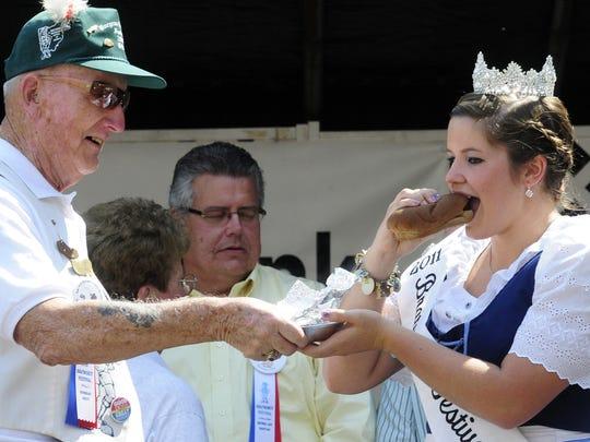Former board of directors member Boyd Long presents the ceremonial first bratwurst to 2011 Bratwurst Queen Richelle Jones.