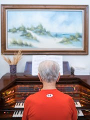 Frank Spellman demonstrates one of the activities he took up, playing the organ, at his home in Gulf Breeze, Florida, Monday, May 30, 2016. Spellman won a gold medal in the 1948 Olympics in London.