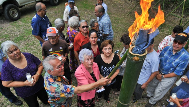 In this file photo, Irene Perez Ploke Sgambelluri-Beruan, dressed in pink, and others light a torch during a memorial service at the Manenggon Memorial Foundation Peace Park in Yona on July 7, 2012.