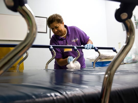 Theresa Foreman, 63, cleans off a bed to have ready for a patient Sunday, November 30 at Lee Memorial Hospital in Fort Myers.