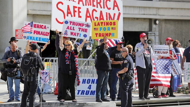 Police stand by as demonstrators who support President Donald Trump's executive orders barring entry to the U.S. by travelers from seven Muslim-majority countries demonstrate across the street from the Tom Bradley International Terminal at Los Angeles International Airport on Saturday.
