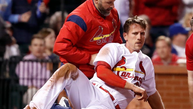 Stephen Piscotty, front, is helped by a trainer after being hit in the head with a ball while scoring during the fifth inning.