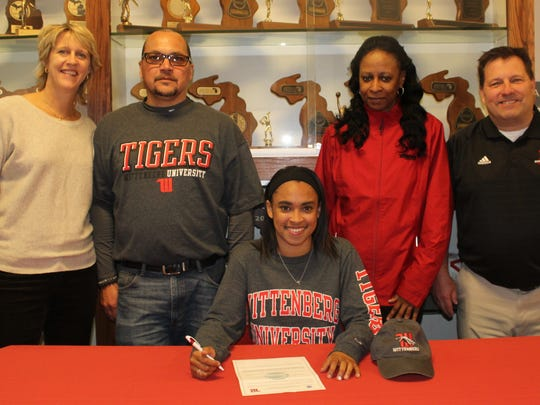 Alexis Johnson (seated) signs her national letter of intent Wednesday under the watchful eye of (left to right) Roeper Principal Lisa Baker, parents Junior and Lashonn, and Roeper AD Ed Sack.