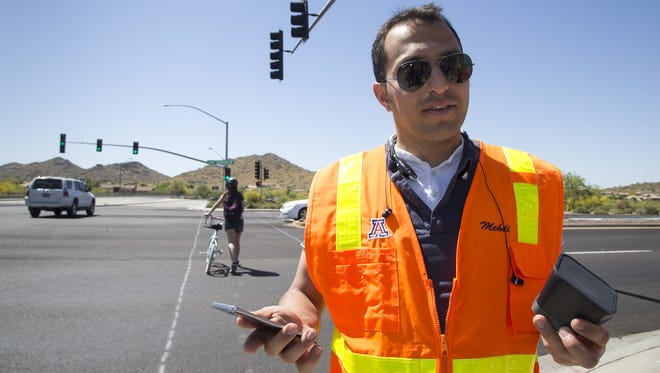 Mehdi Zamanipour, of the Federal Highway Administration, demonstrates how the SMARTDrive pedestrian crosswalk app works at an intersection in Anthem on April 18, 2017.