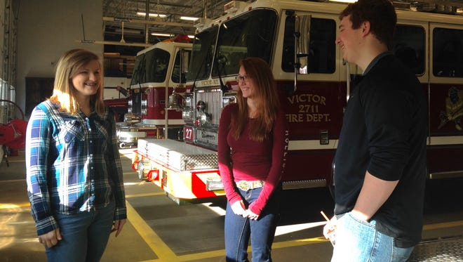 From left to right, Amanda Simonds, Kyleigh Tice, and Michael Murphy talk in the Victor Fire Department station.