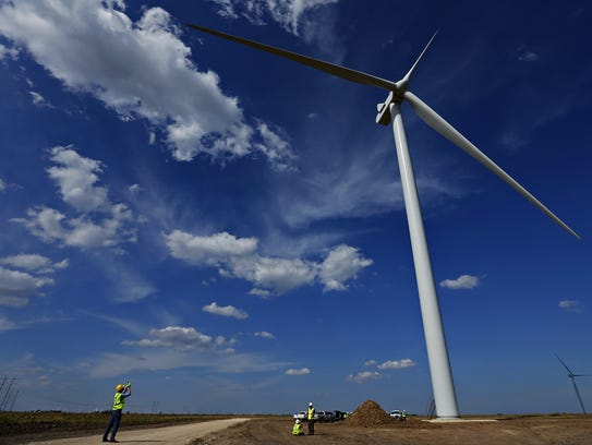 An individual photographs a wind turbine during a September
