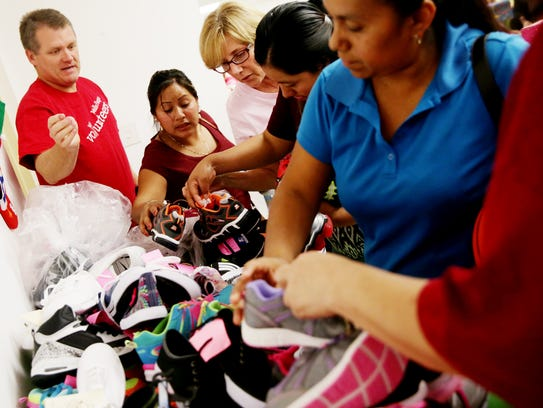Volunteers help parents pick out shoes for their children