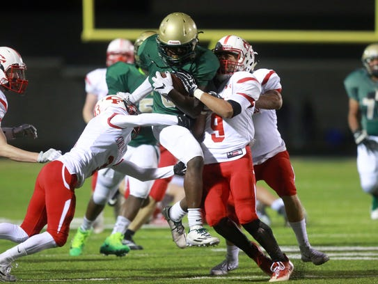 West High's Trumell Roberts fights his way down field