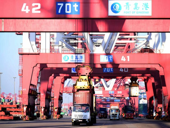 Trucks move shipping containers at a port in Qingdao
