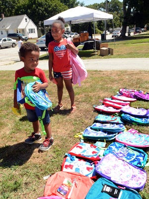 Devon Dixon, 3, and Aaliyah Dixon, 6, get free backpacks Monday on Pembroke Avenue in Norwich. Tim Strong arranged free school supplies, basketballs, masks, pizza and more to give back in his old neighborhood. See videos and more photos at NorwichBulletin.com