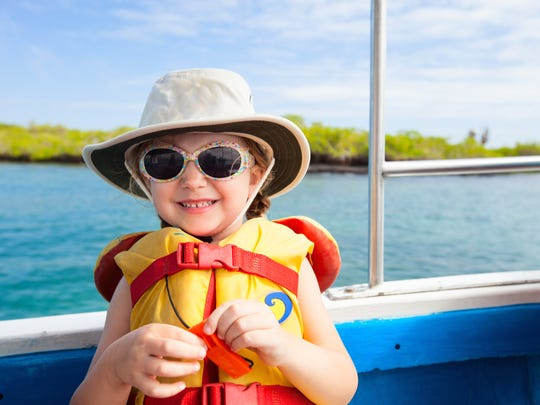Adorable little girl in a life jacket travelling on boat