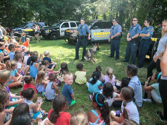 Union County Sheriff's Officer Ashley Current talks to campers about working with her Patrol Narcotics K-9, Sam, as Clark Police, Union County Sheriff's Officers and NJ State Police helicopter visit the Featherbed Lane Day Camp in Clark on Aug. 11, 2016.