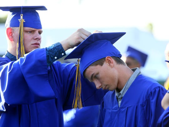 Devin Seaters, left, helps put the tassel on the cap for Gabe Brown before the commencement on Thursday evening.  ///Anderson Union High School, Class of 2017 Commencement on Thursday, June 1st, 2017, in Bob Reid Stadium. There are 112 graduates  receiving their diplomas on Thursday evening. /// (Photo for the Record Searchlight by Hung T. Vu)
