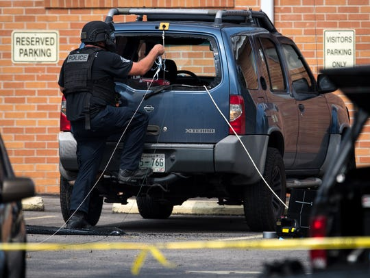 Police use rope and pulleys to remove items from the