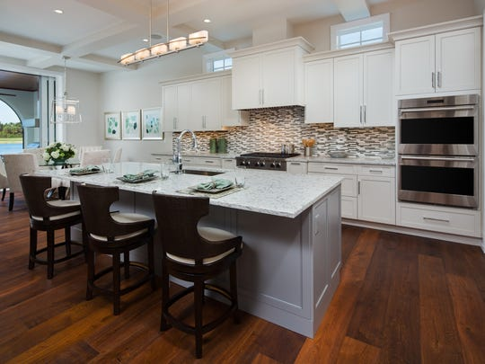 A chef-level kitchen at the Highlands model home in Villa d'Este features quartz counter tops, a custom backsplash highlight, stainless steel double oven, undermount sink, island seating and walk-in pantry.