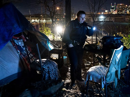 Nashville Metro police officer Kendra Cowper checks to see if a homeless camp is occupied on Dec. 27, 2017 as MNPD officers offered homeless individuals rides to shelters as temperature fell below freezing.