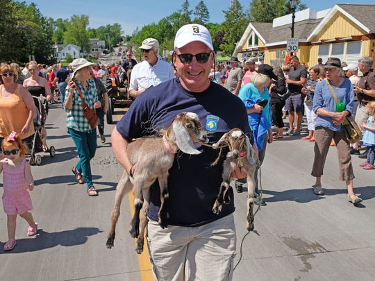 Lars Johnson carries two Nubian baby goats in the annual