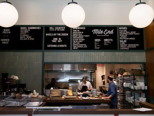 The Mile End Delicatessen has an old-school menu board and table and bar seating for dine-in customers.