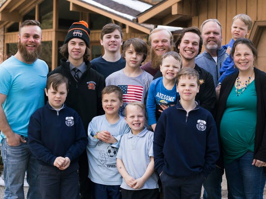 In this Friday, Feb. 16, 2018, photo, the Schwandt family poses for a portrait in front of their home in Grand Rapids, Mich. The only member not pictured is Brandon, 18. The Schwandt family has 13 sons and have welcomed a 14th into the family. The couple's latest addition was born Wednesday evening, April 18 five days before the baby's expected due date.