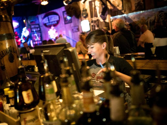 Melissa McMahan, general manager and bartender, rings up a customer's order at Whiskey Bent Saloon on Wednesday, May 23, 2018, in Nashville.