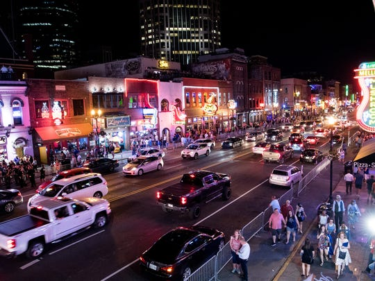 Traffic passes down Broadway in Nashville on Thursday, May 24, 2018. Broadway in recent years has attracted major corporate investment and doled out lucrative licensing deals to country stars such as Blake Shelton and Dierks Bentley to open name-branded bars.
