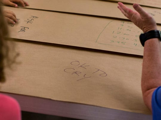 """""""OK to cry"""" is written on the table during Camp Evergreen"""