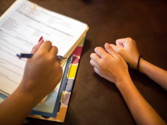Justine Harrison, Hamilton County Children's Services caseworker, goes over a questionnaire with a 9-year-old girl in foster care in rural Lawrence County, Ohio.