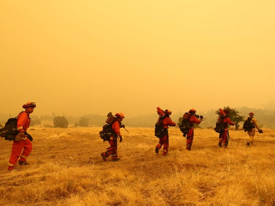 Hotshot firefighters walk on a field to build a defensive