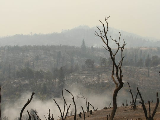 Smoke rises from a skeletal landscape in the immediate aftermath of the Carr Fire around Redding.