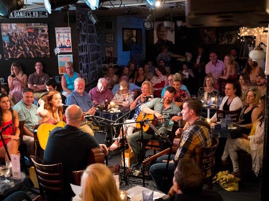 Musicians sit in the center of the room surrounded by the audience at the Bluebird Cafe in Nashville.