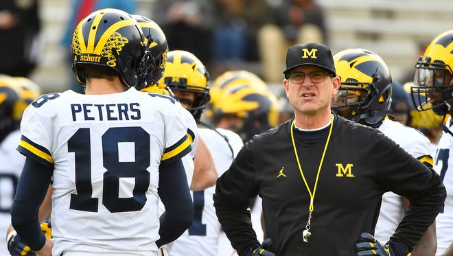 Michigan coach Jim Harbaugh talks with quarterback Brandon Peters (18) before of U-M's 35-10 win on Saturday, Nov. 11, 2017, in College Park, Md.