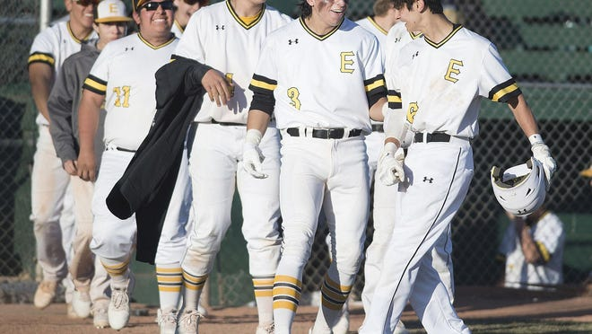 East High School's Nico Cristelli, right, celebrates with teammates after crossing the plate after his bunt resulted in three runs during their game againt Palmer on Hobbs Field in 2018.