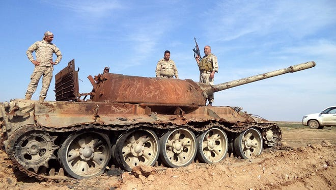 Iraqi soldiers stand on a damaged tank during fighting against Islamic State militants near Tikrit, northern Iraq, Feb. 24, 2015.  Iraqi troops broke a siege by the militants on a residential compound in western Iraq that had denied hundreds of families access to food and medical supplies, officials said.