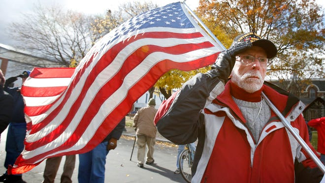 Vietnam War veteran Michael Claprood, of Elmira, stands at attention Friday while bugle call taps is played during the Veterans Day ceremony at Wisner Park in Elmira. Claprood served in the Navy from 1967 to 1969 and was stationed in the Gulf of Tonkin.