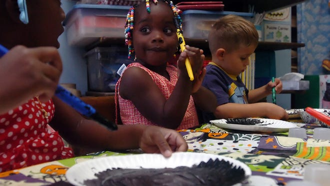 In this file image from October 2006, Arie Wiggins looks at Stephanie Jacinthe as D.J. Brumley, right, works on a Halloween craft at Suncoast School in Vero Beach. The three children were part of the voluntary pre-kindergarten program at the school, which adequately prepared all of its students for kindergarten the last time the state graded preschools.