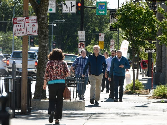 People walk along Fifth Avenue Wednesday, Sept. 14,