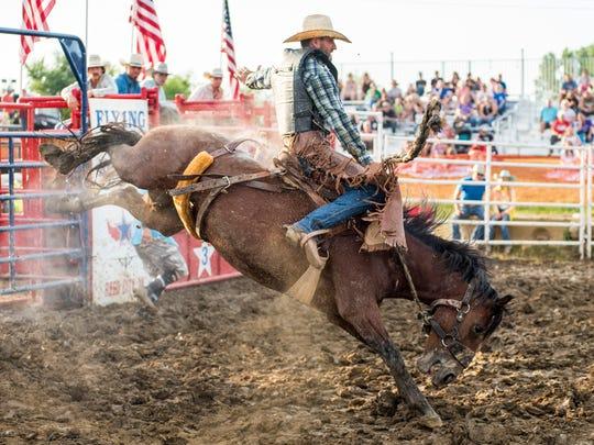 A cowboy rides a bucking horse Monday, July 16, 2018,