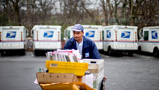In this Feb. 7, 2013 file photo, a U.S. Postal Service letter carrier gathers mail to load into his truck before making his delivery run in the East Atlanta neighborhood in Atlanta. The cost of mailing a letter is going down. Beginning Sunday, April 10, 2016, the price of a first-class stamp drops two cents, to 47 cents. The reduction is the result of an expiring surcharge that had been put in place in January 2014 to help the beleaguered Postal Service recoup $4.6 billion in losses dating back to the Great Recession.
