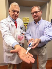 Dr. Vic Tomlinson, left, holds a clear packet of rectum