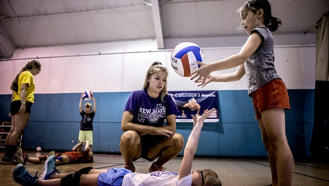 Megan Stanton helps Aubrey Winters and Adrianne Pethtel with their setting skills at the New Wave Volleyball camp Thursday morning.