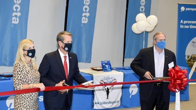 Georgia Gov. Brian Kemp and his wife, Marty Kemp, left, cut the ribbon along with Senior VP and General Manager, Perspecta's Defense Group Jeff Bohling, right, during the grand opening/ribbon-cutting of the Perspecta office at the Georgia Cyber Center Tuesday afternoon October 6, 2020 in Augusta, Ga.