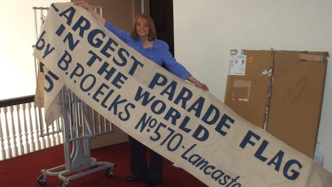 Kathy LeVeck, marketing director of the Fairfield County Visitors & Convention Bureau, holds the banner that identifies the parade flag that belonged to Lancaster's Elks Lodge No. 570.