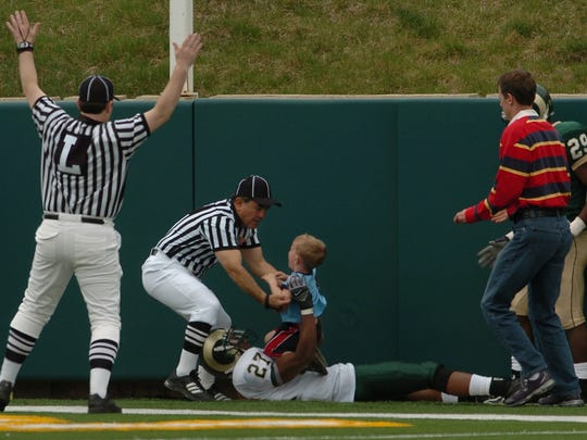Former CSU wide receiver George Hill hands an injured Caden Thomas to an official after Hill crashed into the boy while falling out of the end zone during the 2007 spring game at Hughes Stadium.