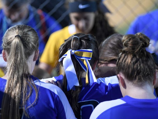 Members of the Jackson Christian softball team join with Scotts Hill players to pray around Scotts Hill's Chelsey Gore who was injured during their game at Jackson Christian's Warner Taylor Field in Jackson, Tenn., on Tuesday, April 18, 2017.