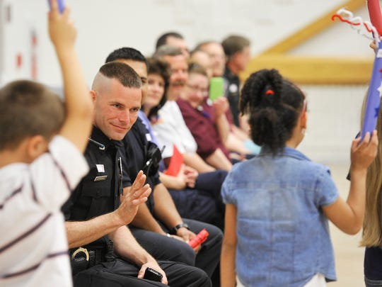 Southern Regional Police Officer Michael Storeman is seen in this file photo from May 24, 2013. He's waving at passing first-grade students at the beginning of an assembly to honor and thank first-responders at Friendship Elementary School.
