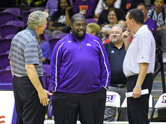 "Harris Wilson, aka ""Coach Black"" (center), game plans with Northwestern State men's basketball coach Mike McConathy (left) and assistant Jeff Moore (right)."